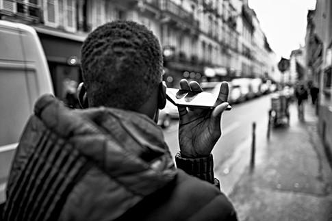 photo dans une rue de paris, un jeune garçon est au téléphone, il marche en tenant son téléphone étrangement, addiction nomophobie