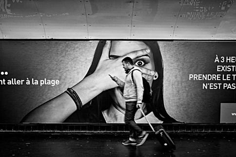 dans un couloir de métro un homme marche avec son téléphone dans la main, c'est un nomophobe, photographie noir et blanc