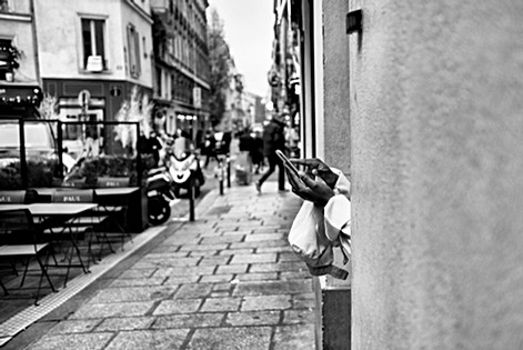 in a street in paris a woman reads a message on her iphone, black and white photo by laurent delhourme