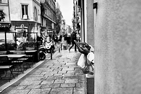 dans une rue de paris une femme lit un message sur son iphone, photo noir et blanc par laurent delhourme