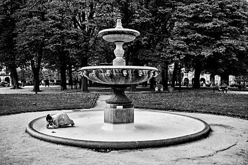 place des vosges à paris, une jeune femme fait des photos couchée au sol dans une fontaine vide d'eau, photographie en noir et blanc par laurent delhourme