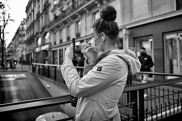 Laurent delhourme - photographe de rue paris - une jeune femme dans la rue se maqille en se regardant dans son iphone