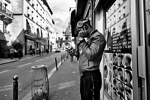 dans une rue de paris, un homme a deux téléphones portables et un casque audio sur la tête, addiction téléphone portable, nomophobie