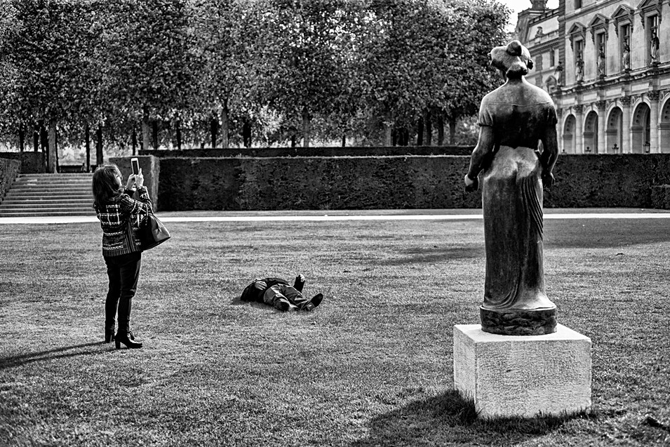in the Tuileries Garden a woman takes photos with her cell phone, her husband sleeps on the lawn, humanist photo by laurent delhourme