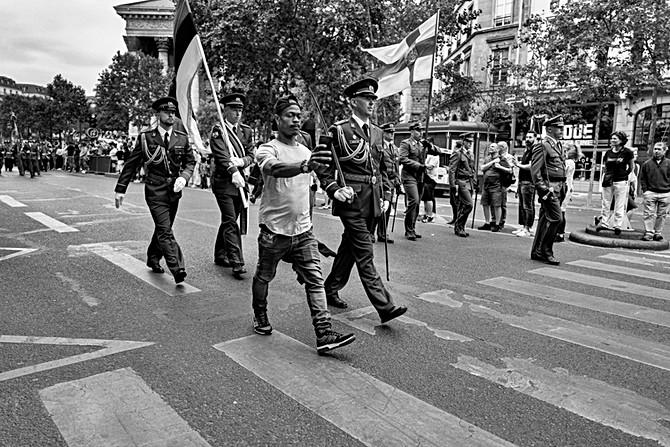 en france à paris pendant le défilé du 14 juillet un homme fait un selfie avec son téléphone avec des militaires, nomophobie