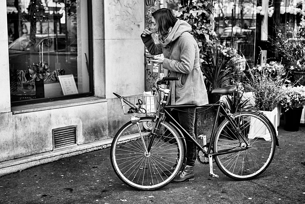 a woman with her bicycle, eats at the same time as she calls a friend, the scene is funny. street photo by laurent delhourme, thematic nomophobia, the photo was taken in paris