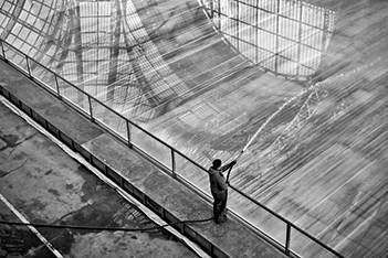 laurent delhourme photographed at the grand palace in paris a man waters an ice rink, the nef is reflected in the mirror.