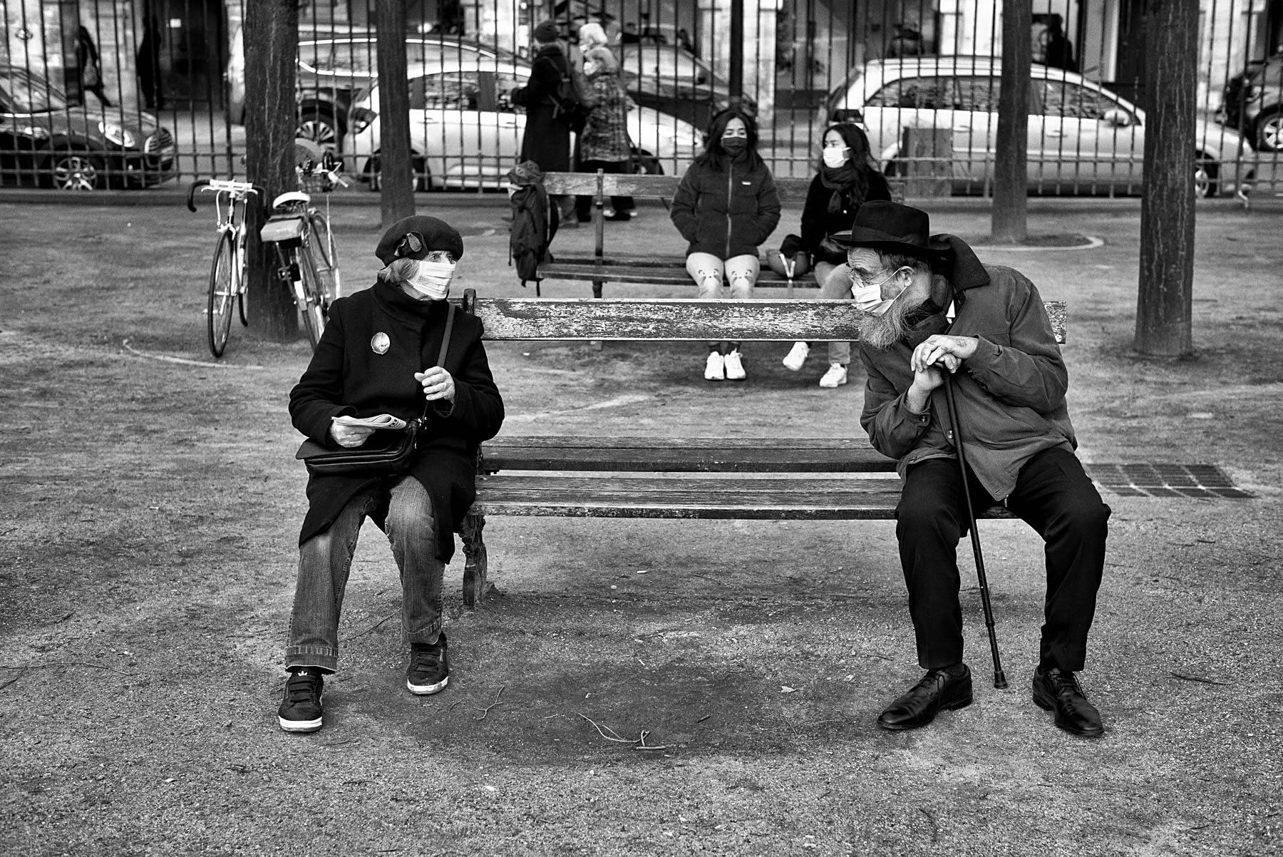 un couple de personnes agés sont assis sur un banc place des vosges à paris, ils discutent, ils ont un masque sur leurs visages, photo noir et blanc