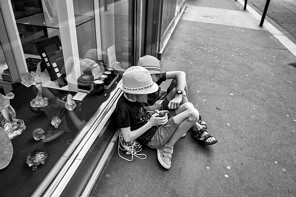 in a street in paris two children play on a mobile phone, street photo by laurent delhourme
