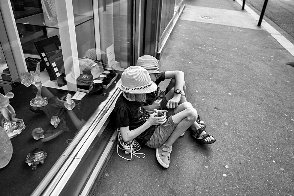dans une rue de paris deux enfants jouent sur un mobilephone, photo de rue par laurent delhourme