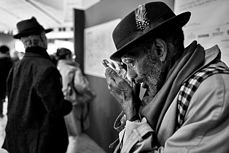 a man with a hat consults his smartphone with a magnifying glass, his face is very close to the screen, author laurent delhourme