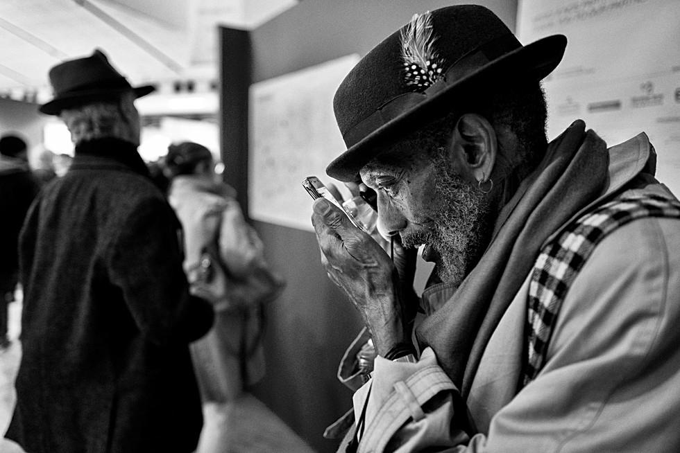 un homme avec un chapeau consulte son smartphone avec une loupe, son visage est très pret de l'écran, auteur laurent delhourme