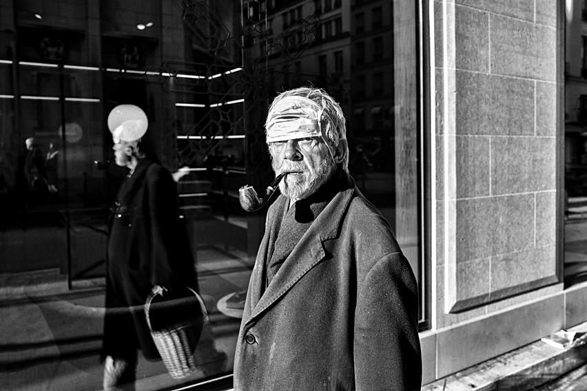 dans une rue de paris un vieil homme marche en fumant sa pipe avec un masque anti covid sur le front, il regarde l'objectif