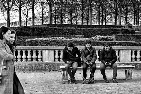 paris jardin des tuileries three men are with their smartphones and do not see two pretty girls pass by, black and white photo
