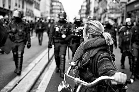 dans une rue de paris en france, des policiers avancent vers une femme qui les prends en photo avec téléphone portable, addiction nomophobie