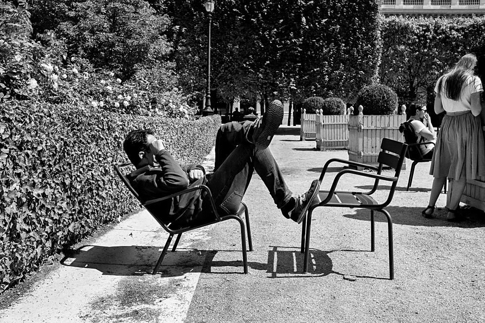 un homme se repose sur une chaise dans le jardin du palais royal à paris, la photo est en noir et blanc, auteur laurent delhourme, photographe de rue français