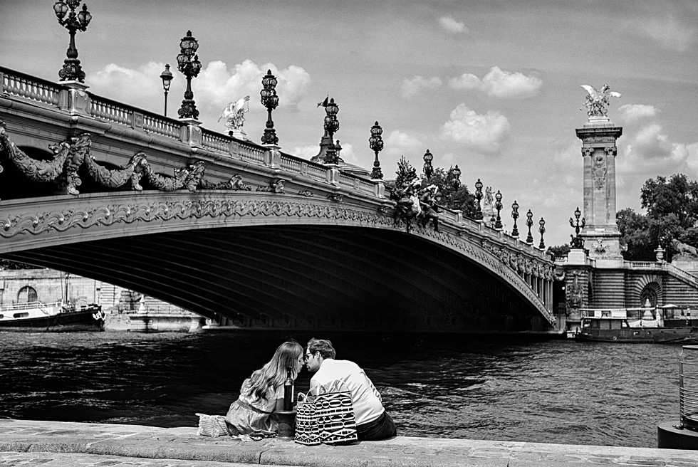 in paris under the alexandre three bridge a couple kiss on the quai de la seine, they have a basket for their lunch, black and white photography