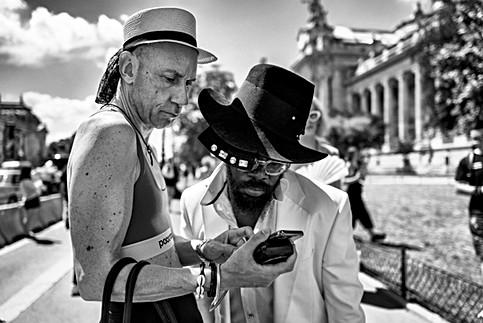 devant le grand palais à paris, deux hommes regardent un téléphone portable