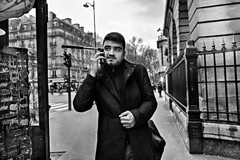 un homme marche sur un trotoir parisien il est au téléphone une perche est encore accrochée à son mobile, auteur laurent delhourme