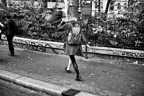 une jeune femme marche dans une rue de paris, elle porte des collants la jambe droite est de couleur blanche et la jambe gauche est de couleur noire, noir et blanc photographie