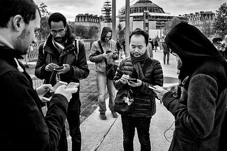 un groupe d'hommes au halles à paris sont avec leurs téléphone portable. ils jouent au pokemon. photo en noir et blanc faite le photographe humaniste laurent delhourme