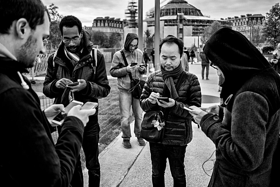 five men are on their mobile phones, pokemon party in the heart of paris in the jardin des halles, they are nomophobes, black and white photography by the humanist photographer laurent delhourme