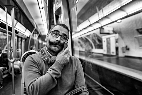 dans le métro parisien un homme assi se brosse sa grosse moustache avec un peigne, photo humaniste noir et blanc