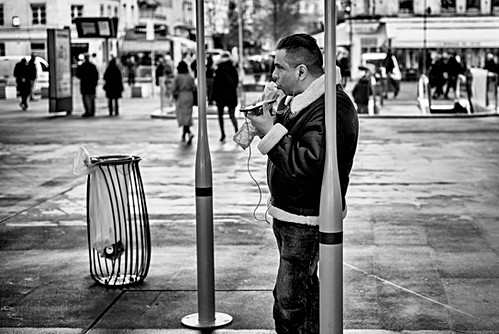 a man eats his sandwich, he talks at the same time with his phone, street photography in paris in black and white.