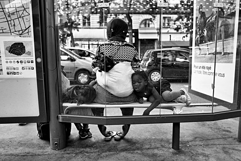 at a bus station a black woman and her three children are waiting for the bus, one of the little girls is sleeping, her face crashes against a window