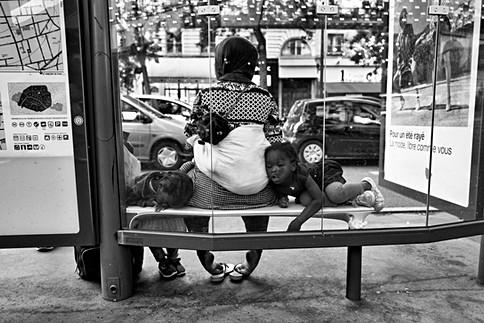 à une station de bus une femme noire et ses trois enfants attendent le bus, une des petites filles dort, son visage s'écrase contre une vitre , photo de laurent delhourme en noir et blanc