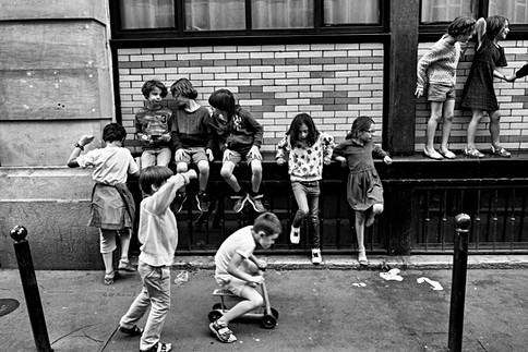 a group of children are playing in front of a building wall in a street in paris, they are happy, a little boy is pushing a skateboard game