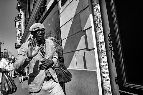 dans une rue de paris un homme noir en costume fais un signe de la main, il marche vite, photo de rue par laurent delhourme