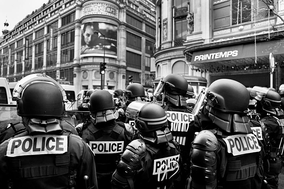 un groupe de policiers devant le grand magasin le printemps à paris, ils sont de dos équipés de casques, photojournalisme en noir et blanc par laurent delhourme