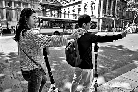 in paris two tourists with pattinettes stopped to take pictures with their mobile phones, rue de paris france, humanist photography by laurent delhourme