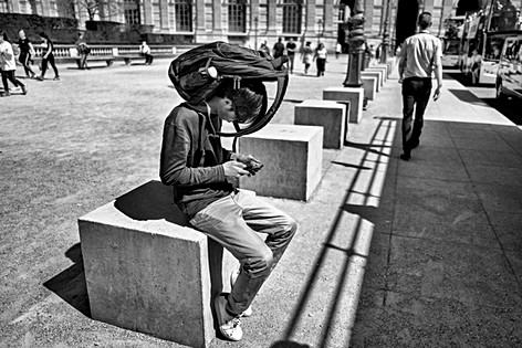 in paris a man consults his phone, it is very hot he has his backpack on his head to provide shade, nomophobia