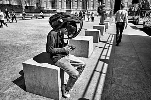 dans paris un homme consulte son téléphone, il fait très chaud il a son sac à dos sur la tête pour faire de l'ombre, nomophobie