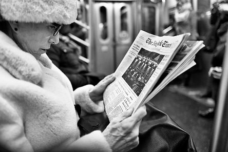 New york subway an old lady sits and reads her newspaper, humanist monochrome photography by laurent delhourme