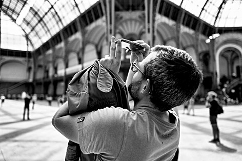 under the nave of the Grand Palais in paris a man takes pictures of the glass roof with his smartphone, black and white photo by laurent delhourme