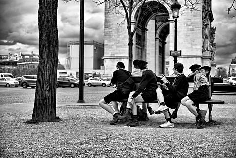un groupe de scouts est assit sur un banc devant l'arc de triomphe à paris, une photo intemporelle en noir et blanc par laurent delhourme au leica M