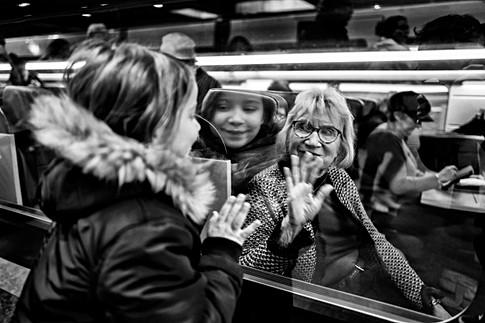 sur le quai d'une gare à paris une petite fille dit aurevoir à sa grand-mere qui est dans le train, il ya beaucoup d'émotion, photographie en noir et blanc à la gare montparnasse