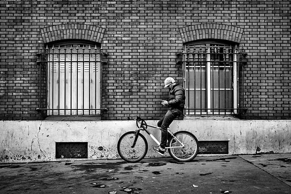 devant un mur de brique un assis sur son vélo passe un sms sur son mobilephone, dans une rue de paris,