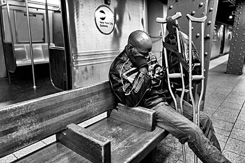 métro de new-york, un homme assis sur un banc tape un mail sur son smartphone, nomophobie addiction téléphone portable