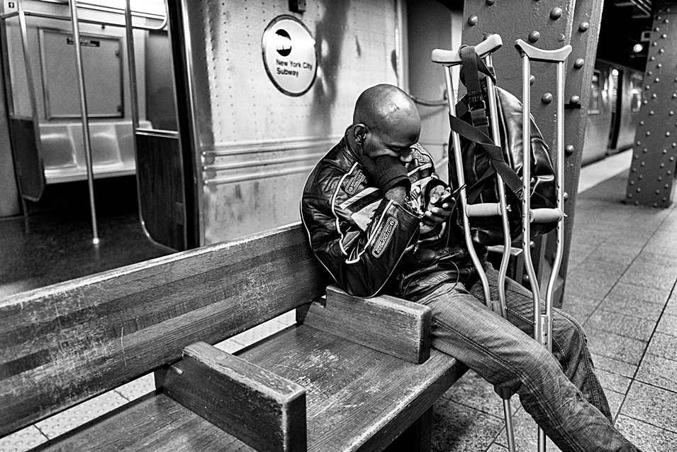 new-york subway, a man sitting on a bench typing an email on his smartphone, nomophobia addiction cell phone
