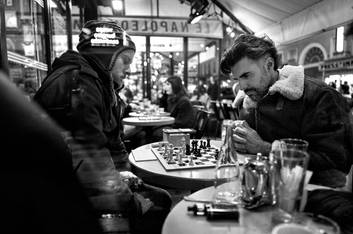 in paris at a cafe terrace two men play chess, nocturnal atmosphere, documentary photo