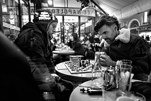 dans paris à une terrasse de café deux hommes jouent aux echecs, ambiance nocture, photo documentaire