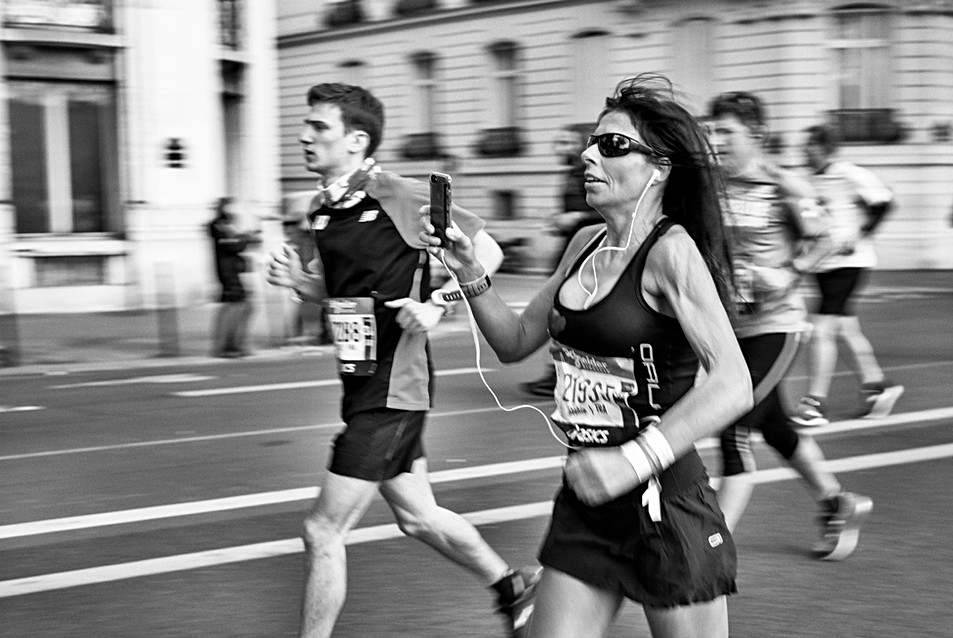 paris marathon a woman runs and films herself with her smartphone, nomophobia, street photo by laurent delhourme