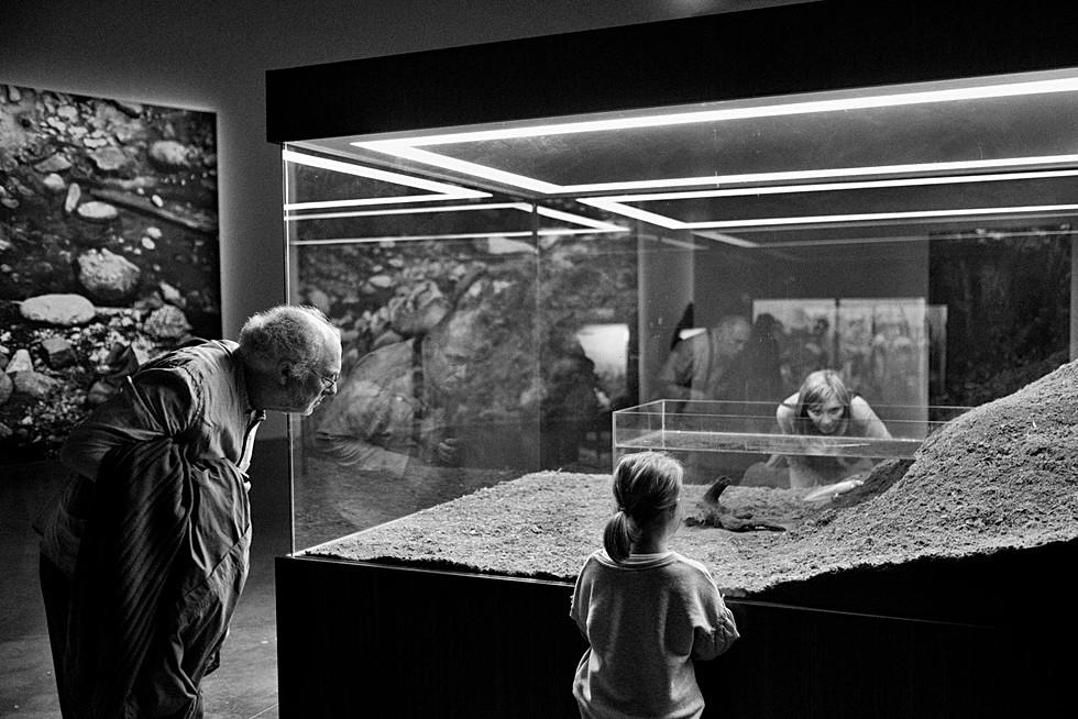 au palais de tokyo à paris trois personnes regardent une oeuvre d'art à travers une vitre, il sont tres currieux, photo en noir et blanc par laurent delhourme