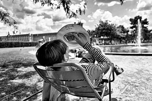 a young man is resting in the tuileries gardens in paris, he is watching a film on his cell phone, author laurent delhourme