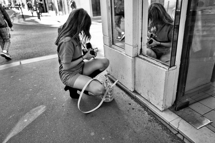 a sexy young woman squatting makes a self portrait in a store window, she has a hasselblad camera, photographed by laurent delhourme in paris