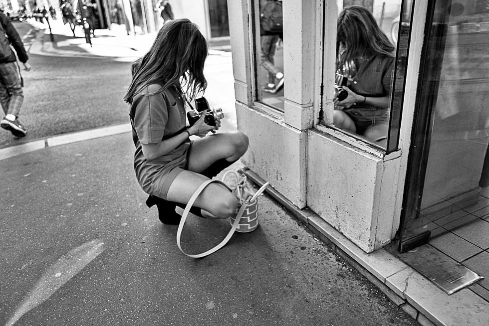 une jeune femme fait un auto portrait à l'angle d'une rue de paris, elle se photographie avec un appareil photo hasselblad, la photo est en noir et blanc, auteur laurent delhourme